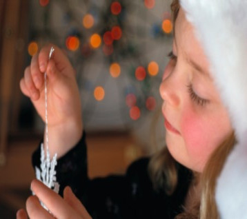 Little girl holding snow flake ornament
